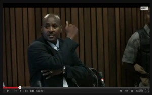 Mangena showing where projectiles and tissue came out of exit wound on arm and sprayed the right chest area
