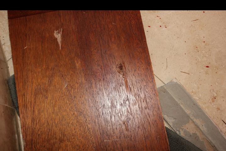 Wood panel and broken tiles in bathroom