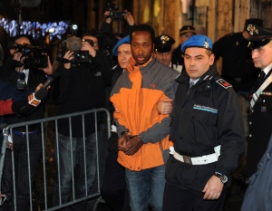 Rudy Guede (C) is escorted from the courthouse at the end of his appeal against the sentence he received in the Meredith Kercher murder trial, in Perugia December 22, 2009. Guede, the Ivorian youth accused of complicity, along with Amanda Knox and Raffaele Sollecito, in the November 2007 murder of British student Kercher was sentenced to 30 years in jail in October 2008 but his appeal has seen his sentence reduced to 16 years. REUTERS/Alessandro Bianchi (ITALY - Tags: CRIME LAW) - RTR28AHA